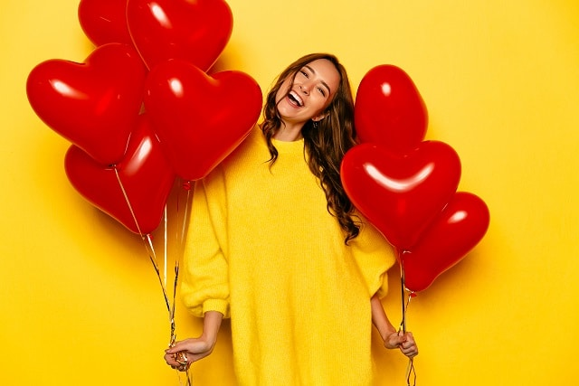 Young attractive girl with long curly hair, in yellow sweater holding red air balloons, posing at camera. St. Valentine's day. Isolated on yellow background.